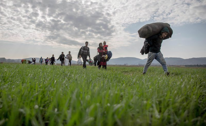Refugees walk across a field in the direction of the refugee camp on the Greek-Macedonian border in Idomeni, Greece, 03 March 2016 (EPA Photo)