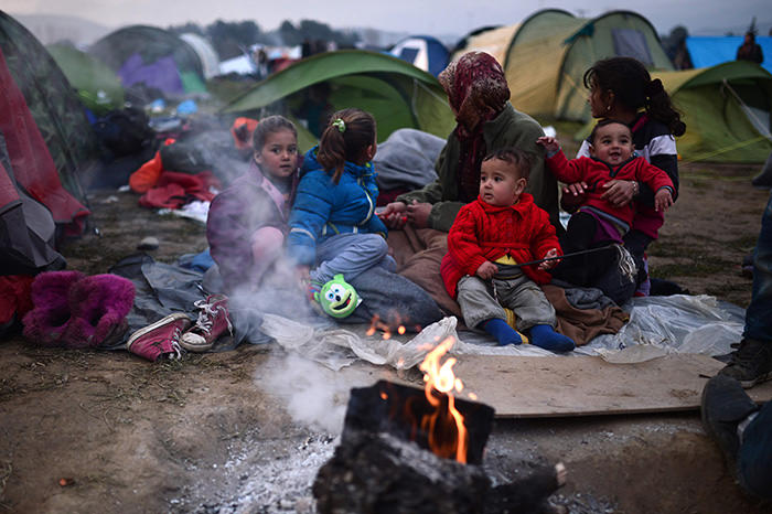 Refugees warm-up by a fire at a makeshift camp along the Greek-Macedonian border near the village of Idomeni on February 28, 2016. (AFP Photo)