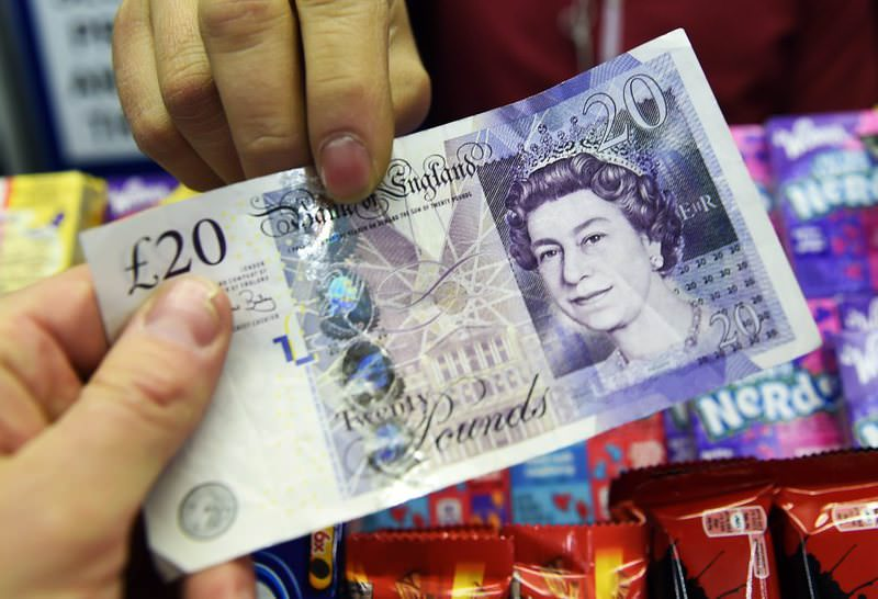 A file photo showing a customer handing over a 20 pound note at a store in London.