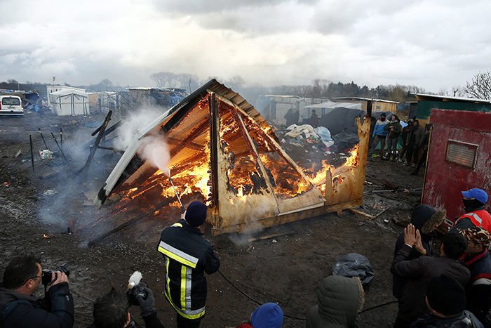 A shelter is set on fire at the makeshift migrant camp, the 'Jungle', as workers assist in the demolition, in Calais, France, 02 March 2016 (EPA Photo)