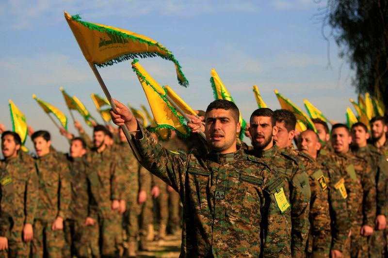 Hezbollah fighters who are considered terrorist by the members of the Gulf  Cooperation Council hold flags in a march.