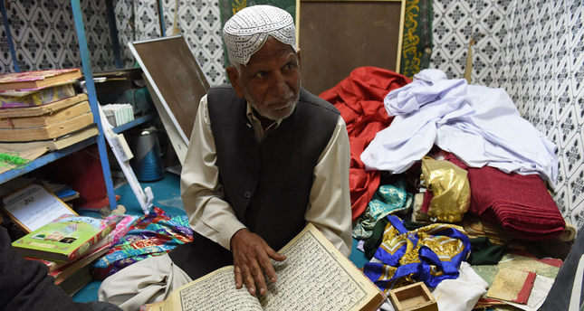 Haji Muzaffar Ali, the administrator of Jabl-e-Noor, examines an old copy of the Quran in a tunnel where ancient copies of the holy book are preserved on the outskirts of Quetta.