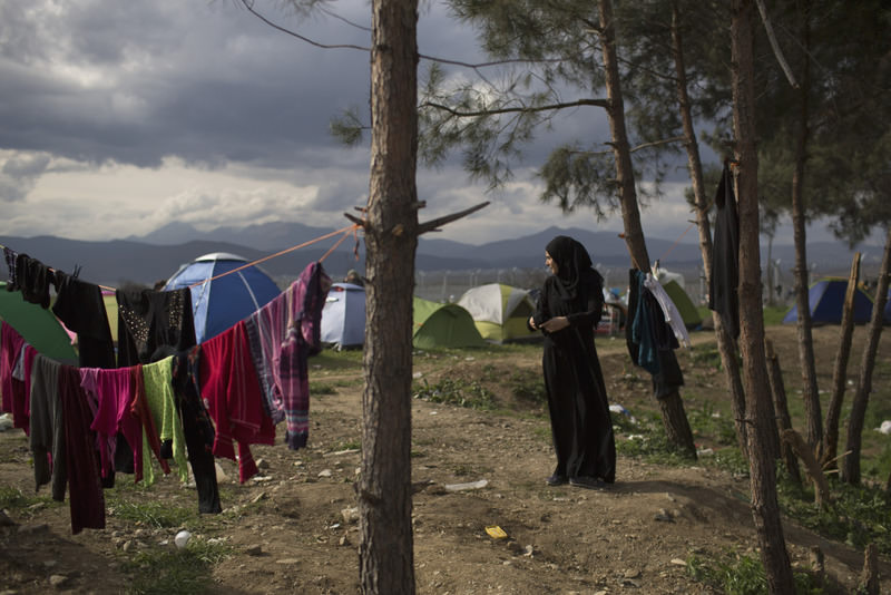 A woman hanging on clothes in a refugee camp where refugees are waiting to be allowed to cross the border into Macedonia in the northern Greek border station of Idomeni. (AP Photo)