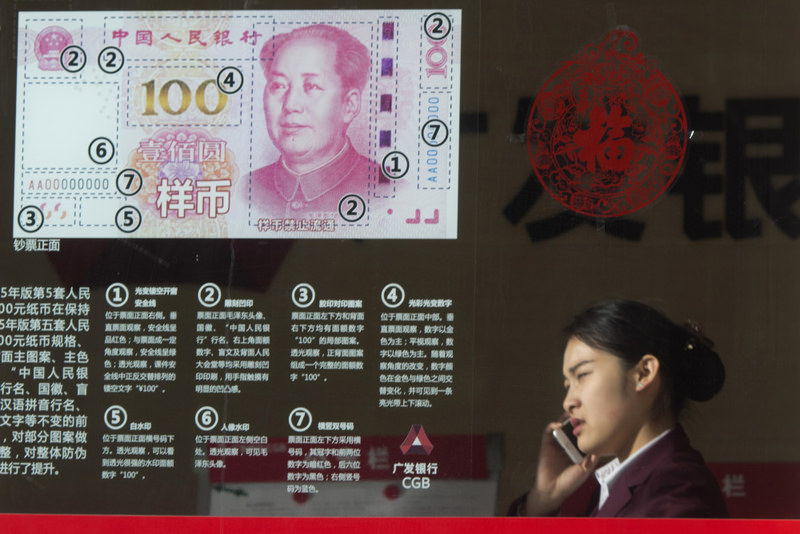 In this Feb. 16, 2016 file photo, a woman speaks on her phone near a display highlighting the new Chinese bank notes at a bank in Beijing. (AP Photo)