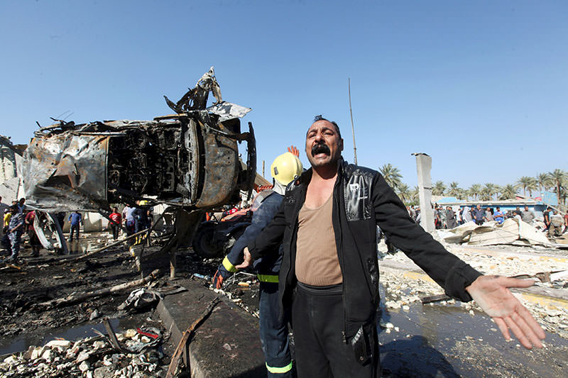 A man reacts at the site of a bomb attack at a checkpoint in the city of Hilla, south of Baghdad, March 6, 2016 (Reuters)