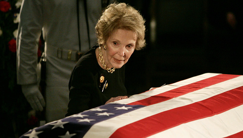 Former U.S. first lady Nancy Reagan touches the casket of her husband, former U.S. President Ronald Reagan as it lies in state in the rotunda of the United States Capitol in Washington in this June 9, 2004 file photo (Reuters Photo)