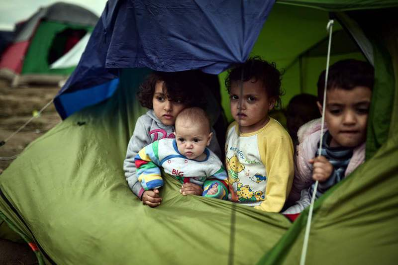 Children sit in a tent in the makeshift camp at the Greek-Macedonian border near the village of Idomeni where thousands of migrants are stranded on March 7.