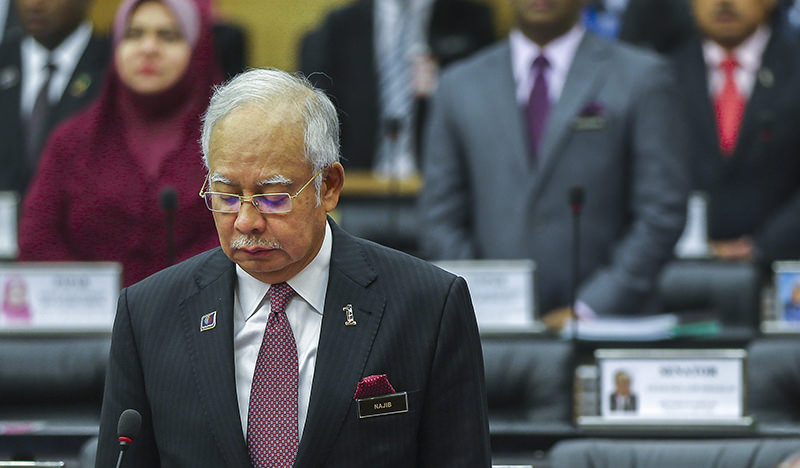 Malaysian Prime Minister Najib Razak observes a moment of silence to mark the second year since the disappearance of Malaysia Airlines flight MH370, at the Parliament in Kuala Lumpur (EPA Photo)