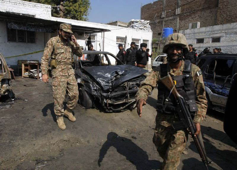 Pakistani soldiers inspect the site of a suicide bombing in Shabqadar on March 7.