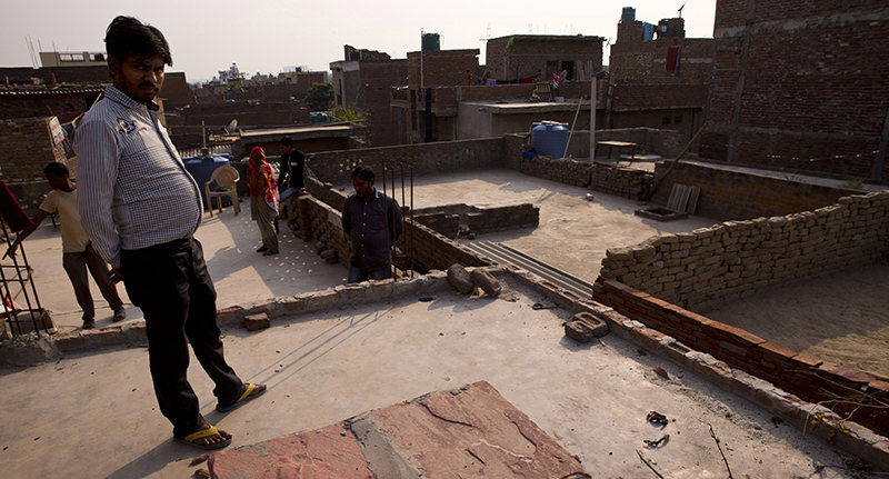 Relatives stand on the terrace of a house where a 15-year-old girl was set on fire after being raped at Tigri village, near Noida, a suburb of New Delhi, India, Tuesday, March 8, 2016 (AP Photo)