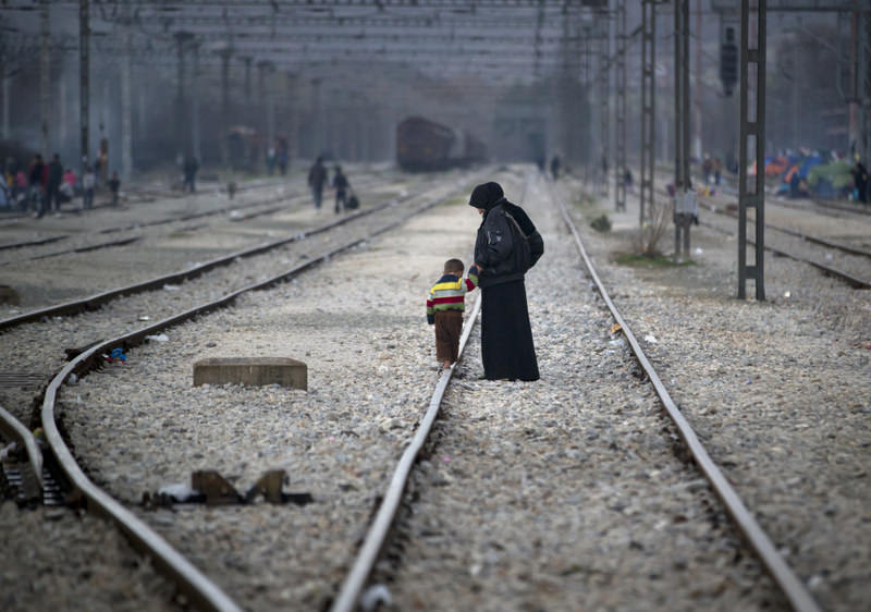 A Syrian woman holding the hand of a toddler walking on a railway track at the northern Greek border station of Idomeni.