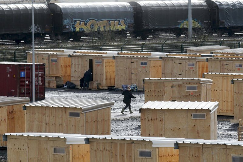 Migrants arrive at a refugee camp with wood humanitarian-standard shelters in Grande-Synthe near Dunkerque in northern France on March 7.