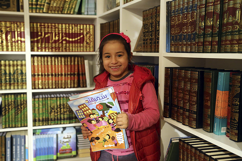 Photo dated Feb. 20, 2016 shows a Syrian refugee child holding a magazine at the Arabic Book Fair 2016 in Istanbul.