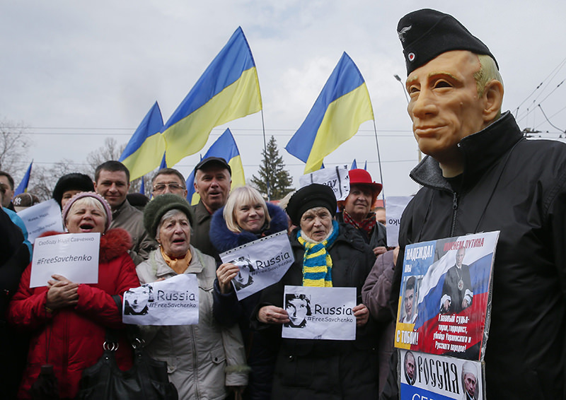 Protesters hold placards reading 'Free Savchenko' near a man wearing a mask depicting Putin during a rally in front of the Russian embassy in Kiev, Ukraine. (EPA Photo)