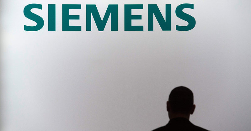 This file photo taken on November 12, 2015 shows an employee of German industrial giant Siemens standing in front of a company logo during a press conference in Berlin.  (AFP Photo)