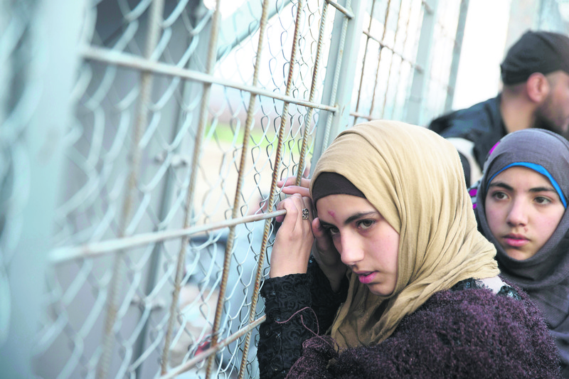A young Syrian woman leans on a door through which refugees enter Macedonia in the Greek border town of Idomeni.