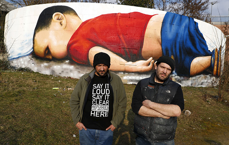 Artists Justus Becker (R) and Ou011fuz u015een stand in front of a huge graffiti artwork of Syrian toddler Aylan Kurdi (Reuters)