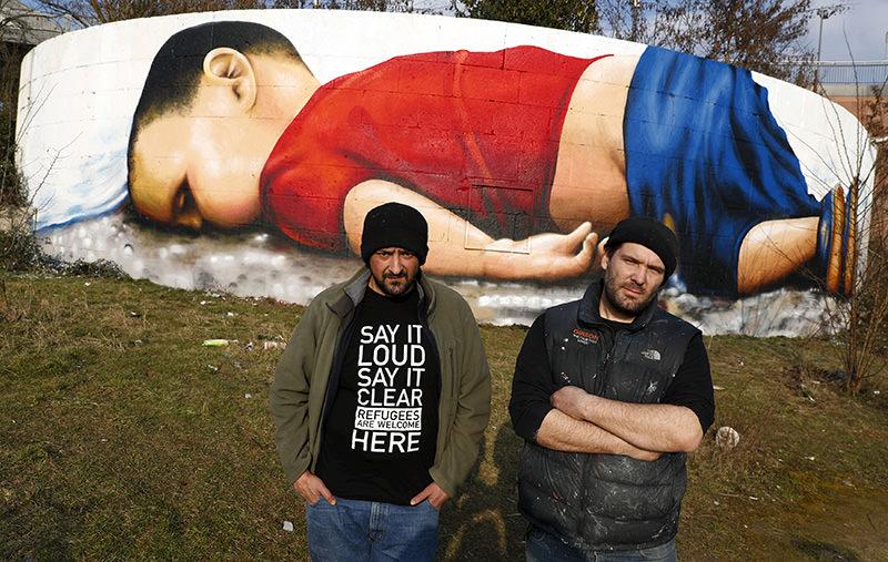Artists Justus Becker (R) and Ou011fuz u015een stand in front of a huge graffiti artwork of Syrian toddler Aylan Kurdi (Reuters)