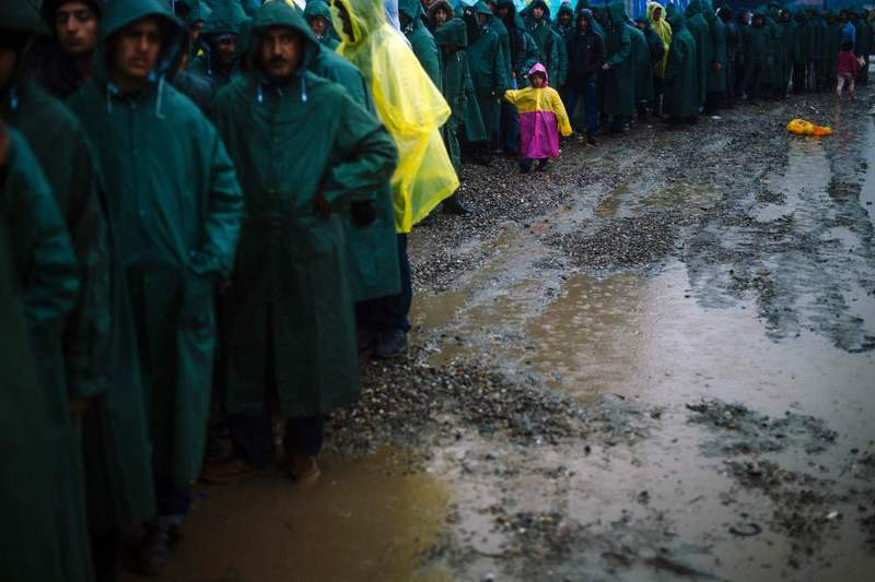 Refugees and migrants queue in the rain for soup in a makeshift camp at the Greek-Macedonian border, near the Greek village of Idomeni.