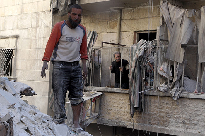 Residents inspect damage after an air strike on the rebel held al-Saliheen district in Aleppo, Syria, March 11, 2016 (Reuters Photo)