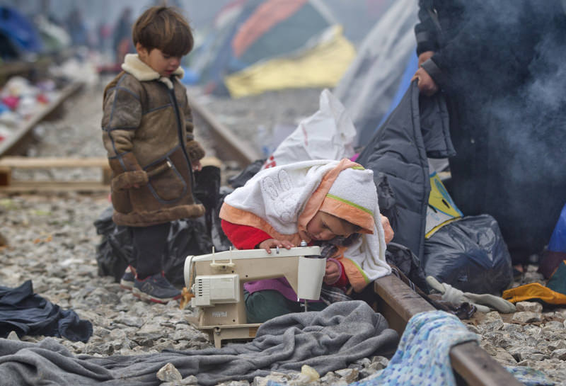A child plays with a broken sewing machine on railway tracks at the northern Greek border station of Idomeni near the Macedonian border.