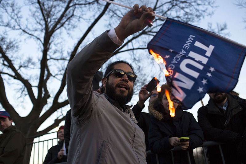 A protester burns a flag outside of the University of Illinois at Chicago Pavilion where Republican presidential candidate Donald Trump cancelled rally. (AFP Photo)