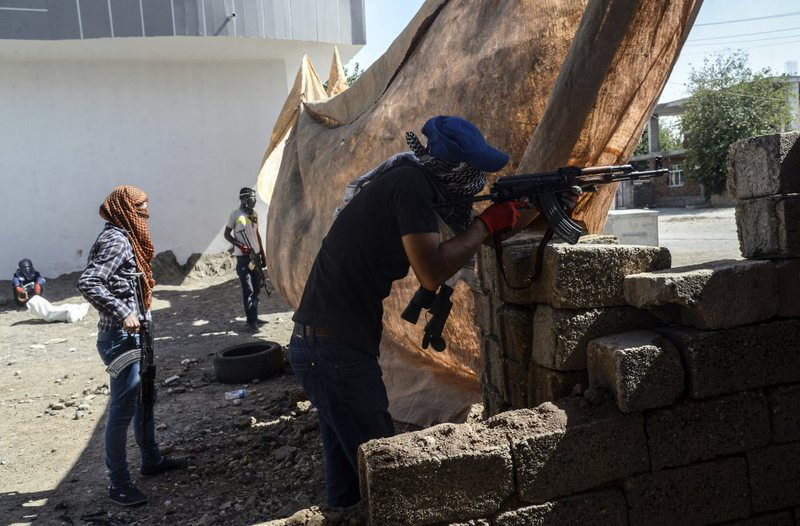 PKK terrorists stand behind a barricade of concrete blocks in the  Bismil district of Diyarbaku0131r.