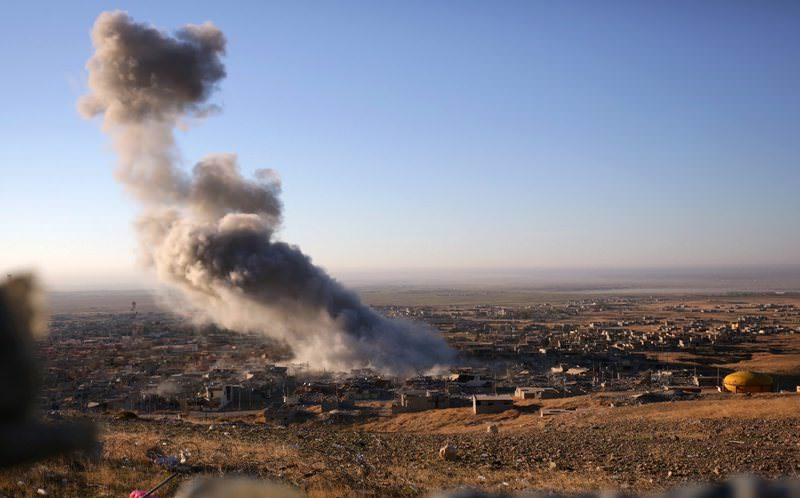Smoke believed to be from an airstrike billows over the northern Iraqi town of Sinjar.