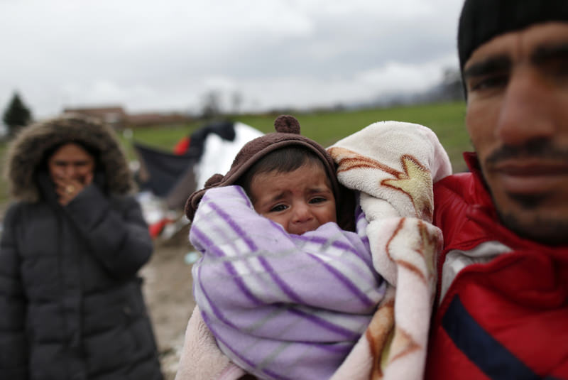 Yousif Shikhmous, a Syrian refugee holds his baby in an improvised camp on the border between Macedonia and Serbia near the northern Macedonian village of Tabanovce on March 11.