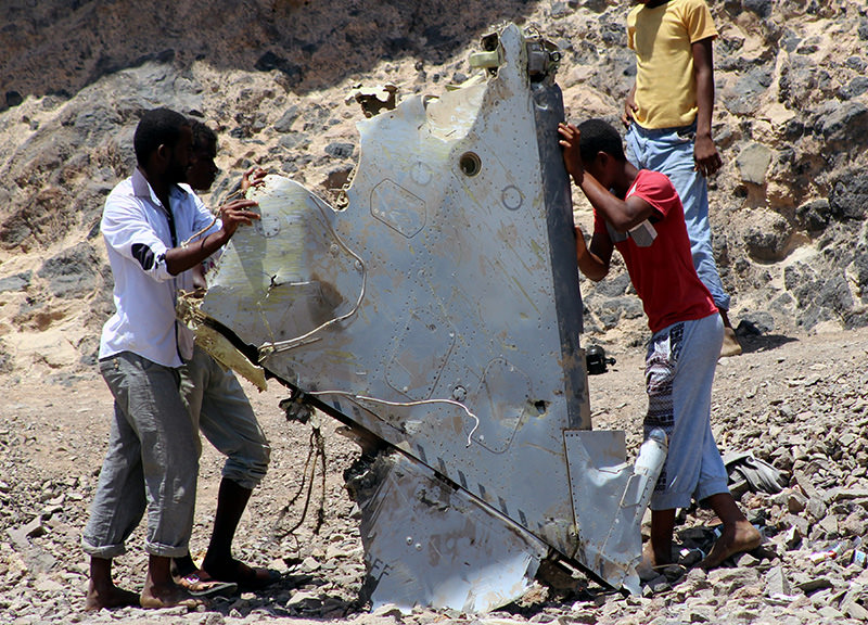 Yemenis hold a piece allegedly belonging to a UAE fighter jet that went missing in the southern port city of Aden, Yemen, 14 March 2016 (EPA Photo)