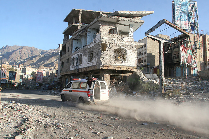An ambulance drives past a building destroyed during recent fighting in Yemen's southwestern city of Taiz March 14, 2016 (Reuters Photo)