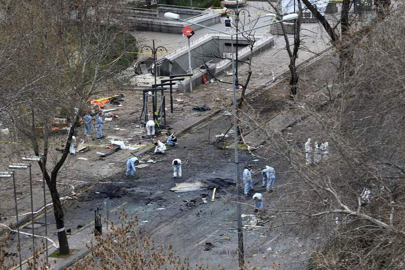 Forensic experts investigate the scene of an explosion on the day after a suicide car bomb ripped through a busy square in central Ankara, killing at least 35 people and wounding 125.