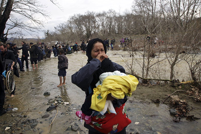 Hundreds of migrants and refugees walked out of an overcrowded camp on the Greek-Macedonian border March 15, 2016. (AP Photo)