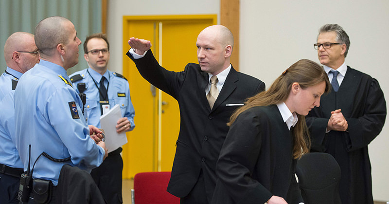 Norwegian mass killer Anders Behring Breivik (C) makes a Nazi salute as he arrives to a makeshift court in Skien prisonu2019s gym on March 15, 2016 in Skien, some 130 km south west of Oslo (AFP Photo)