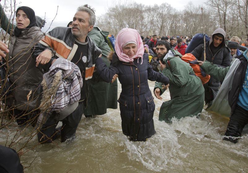 A woman cries as she crosses a river along with other migrants, north of Idomeni, Greece, attempting to reach Macedonia on a route that would bypass the border fence on March 14. (EPA Photo)