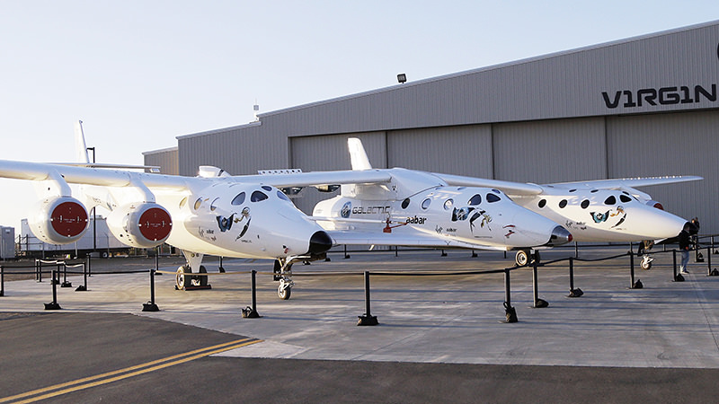 In this Sept. 25, 2013, file photo, the first SpaceShipTwo is seen suspended at center beneath its twin-fuselage mother ship at the Virgin Galactic hangar at Mojave Air and Space Port in Mojave, Calif. (AP Photo)