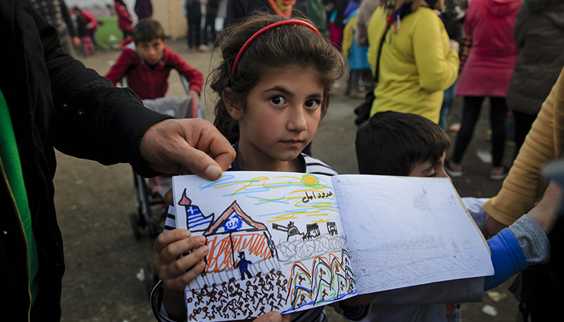 Shaharzad Hassan, 8 year-old from the Syrian city of Aleppo poses with a drawing she made at the northern Greek border station of Idomeni, Friday, March 11, 2016. (AP Photo)