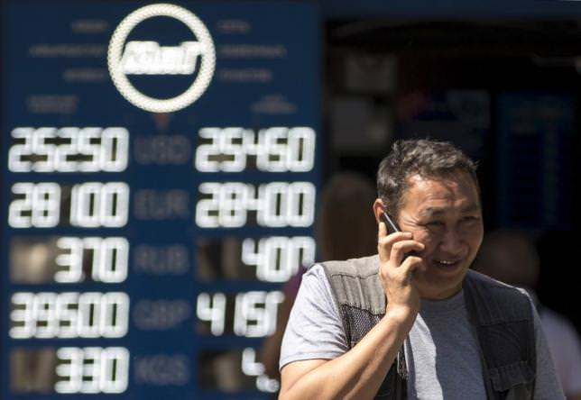 A man talks on his mobile phone as he walks past a board showing currency exchange rates in Almaty, Kazakhstan, August 20, 2015. (REUTERS Photo)