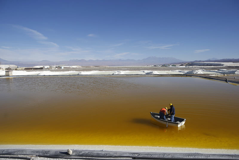 Workers use a boat to take samples from a brine pool at the Rockwood Lithium Plant on the Atacama salt flat, the largest lithium deposit currently in production, in the Atacama desert of northern Chile.