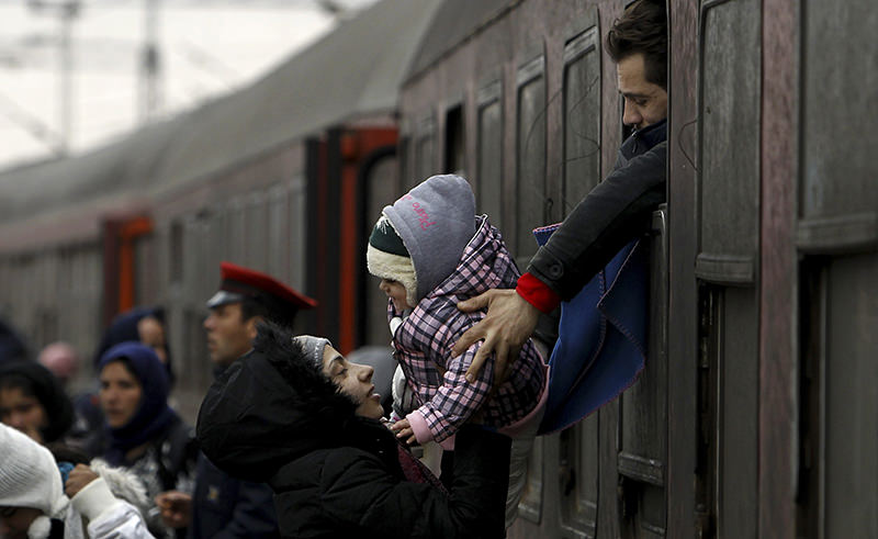 A refugee man passes a baby to a woman from a train window, upon their arrival at the transit center for refugees near northern Macedonian village of Tabanovce, Wednesday, Feb. 10, 2016 (AP Photo)