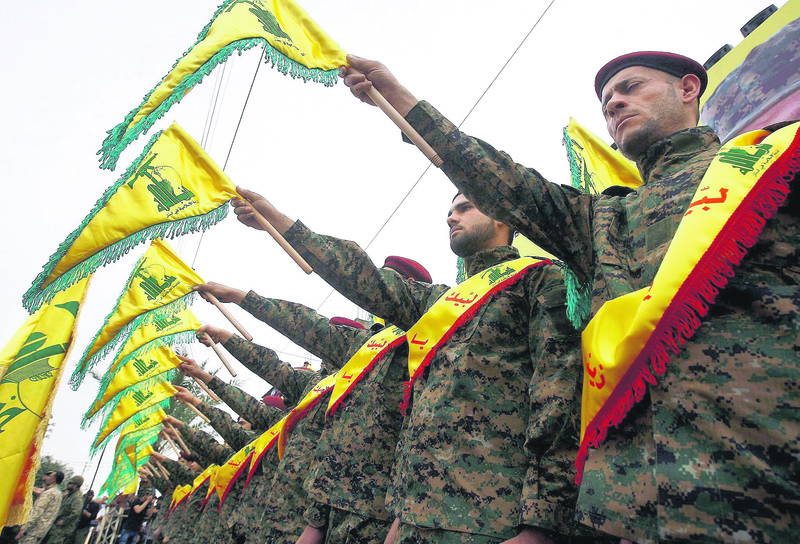 Hezbollah fighters hold the group's flag as they attend a ceremony in South Lebanon.