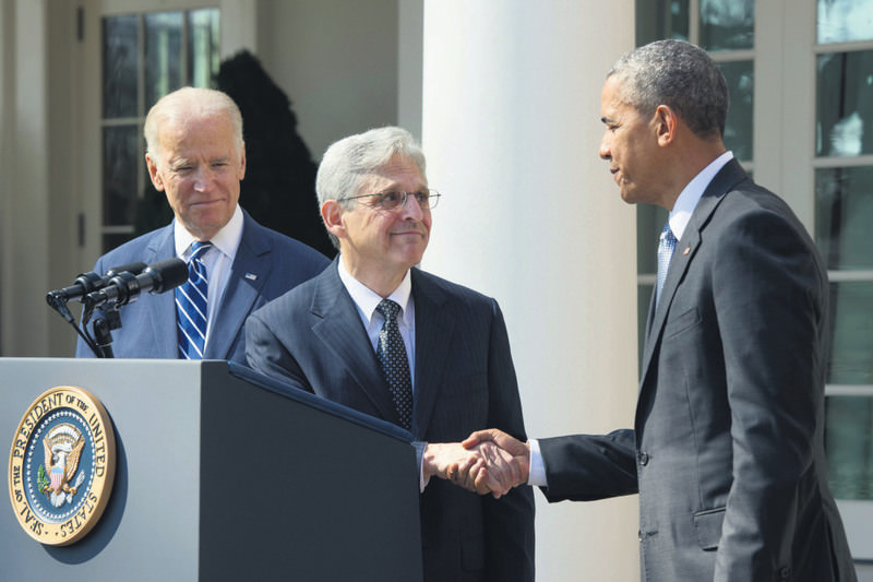 Vice President Joe Biden (L) looks on as Supreme Court nominee Merrick Garland (C) shakes hands with President Obama in front of the White House on March 16.