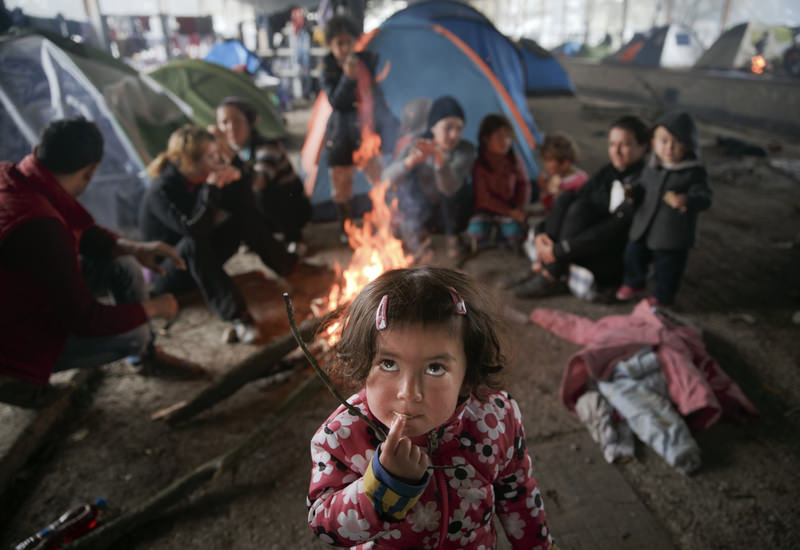A child eats as others sit around a fire in a railway repair hangar where people have set up their tents at the northern Greek border point of Idomeni on March 18. (AP Photo)