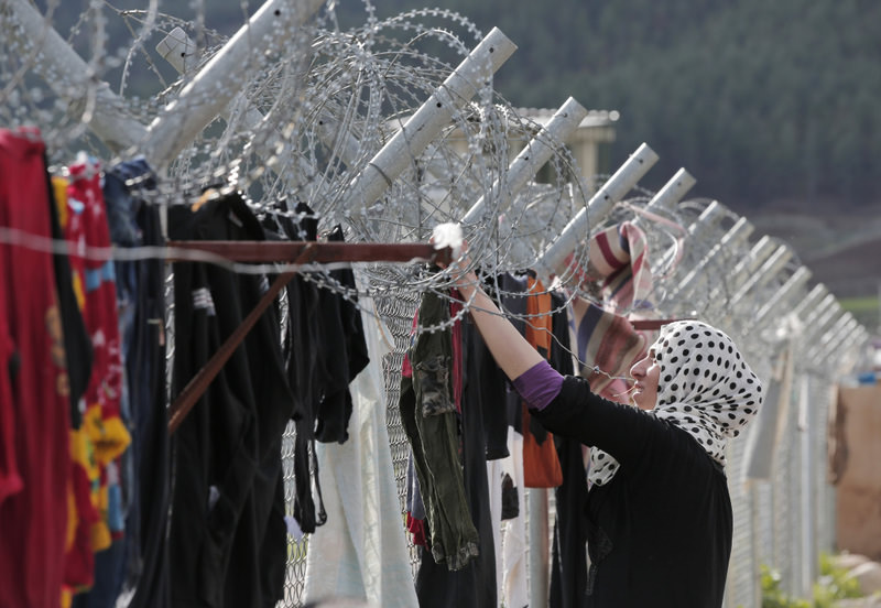A Syrian refugee hanging clothes to dry on a barbed-wire fence at a camp for Syrian refugees in Islahiye, Gaziantep province, southeast Turkey. (AP Photo)