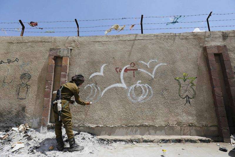 An armed Yemeni soldier paints graffiti in support of peace in the war-affected country on a wall in Sanaa. (EPA Photo)