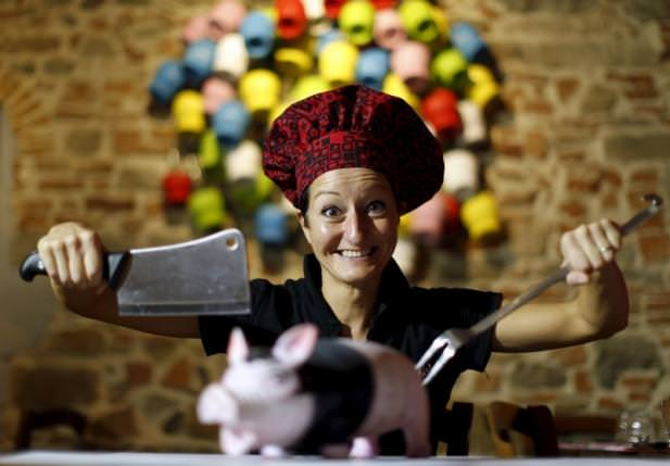 Italian chef Cristina Palanti poses with a meat cleaver and cooking fork hovering over a plastic pig figurine at the 'L'e'Maiala' restaurant in Florence on October 6, 2012. (REUTERS Photo)
