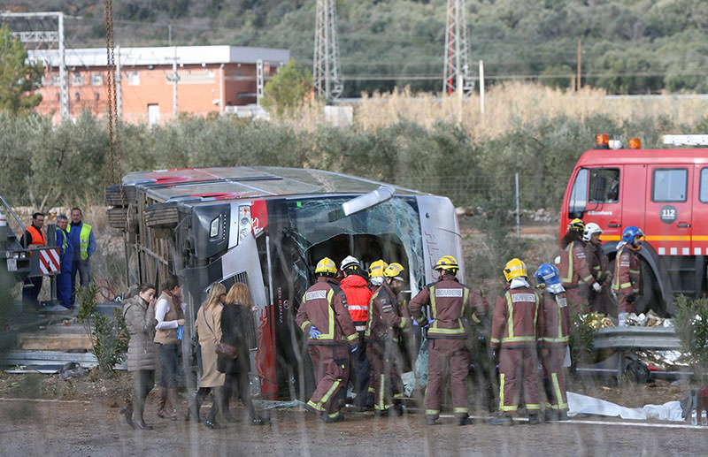 Firemen work at the site of a coach crash that has left at least 14 students dead at the AP-7 motorway in Freginals, in the province of Tarragona, 20 March 2016 (EPA)