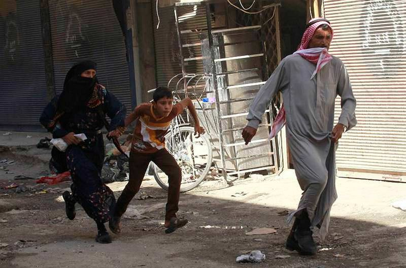 In this file photo, residents of Raqqa escape after an airstrike, conducted by the Syrian regime.