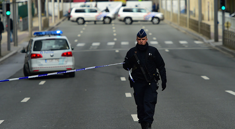 A police officers sets a security perimeter near Maalbeek metro station, on March 22, 2016 in Brussels, after a blast at this station near the EU institutions caused deaths and injuries. (AFP Photo)
