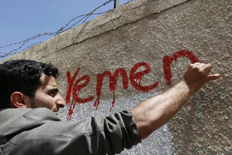 A Yemeni activist writes 'Yemen' at a graffito in support of peace in the war-affected country, at a wall along a street in Sanaa.